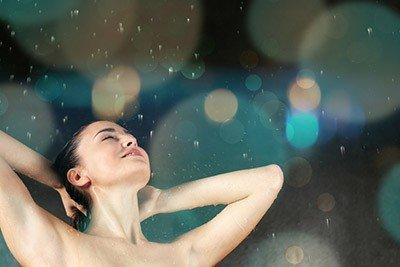 Schöne junge Frau unter der Dusche